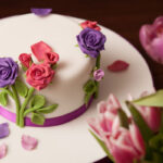 White cake with pink and purple roses